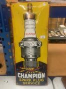 A RETRO METAL 'CHAMPION SPARK PLUG SERVICE' SIGN 70CM X 30CM