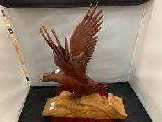 A WOODEN CARVED BIRD OF PREY CATCHING A FISH