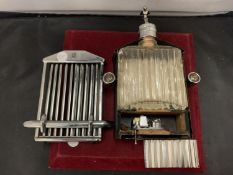 A CHROME AND BLACK METAL GLASS DRINKS FLASK IN THE FORM OF A BENTLEY GRILL, INCORPORATING A MUSIC