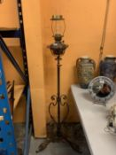 A VINTAGE OIL LAMP ON AN ADJUSTABLE METAL STAND