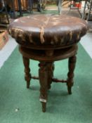 A VINTAGE ROUND LEATHER BUTTONED PIANO STOOL
