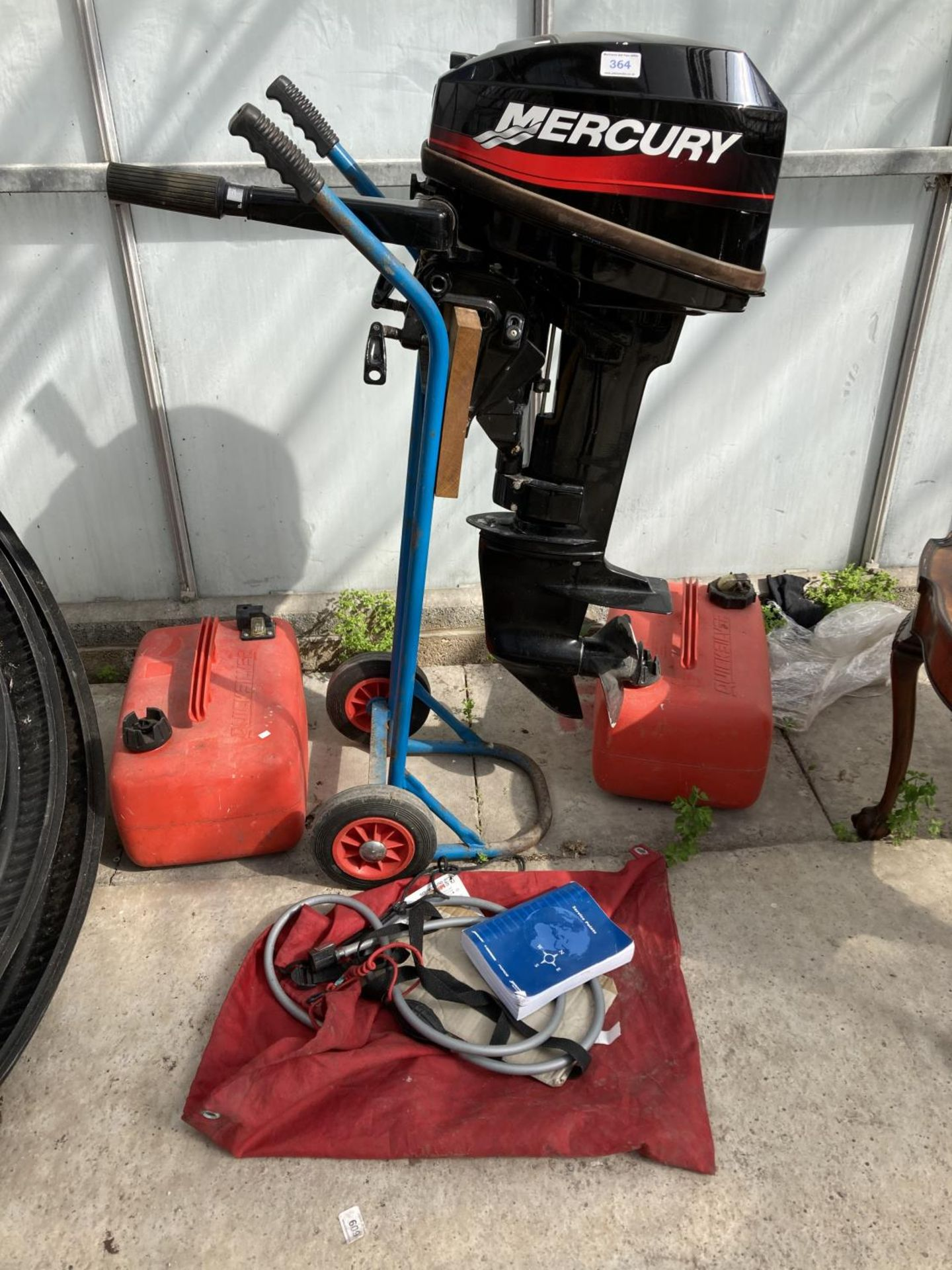 A MERCURY 15 OUTBOARD MOTOR, FUEL CANS, MANUAL AND TROLLEY NO VAT