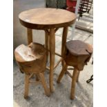 A WOODEN TABLE AND TWO LOG TOPPED STOOLS NO VAT