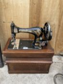 A VINTAGE SINGER SEWING MACHINE WITH WOODEN CARRY CASE