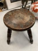 A SMALL MAHOGANY FOUR LEGGED STOOL WITH TEXTURAL DECORATION H: 21CM