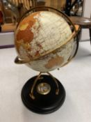 A DECORATIVE DESK GLOBE WITH BRASS DETAIL AND INTEGRATED COMPASS IN THE BASE H: APPROXIMATELY 31CM