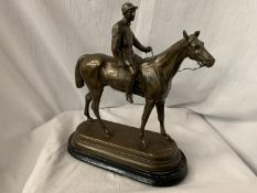 A SPELTER FIGURINE IN THE FORM OF A HORSE AND JOCKEY SIGNED C VALTON