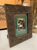 A CARVED WOODEN TABLE PICTURE FRAME WITH SILVER DETAIL 21.5CM X 26.5CM