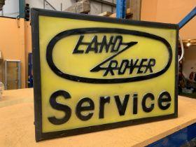AN ILLUMINATED ' LAND ROVER SERVICE' SIGN