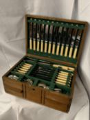 A LARGE OAK BOX WITH WOODEN CROSSBANDING DETAIL CONTAINING SILVER PLATE FLATWARE (TWELVE PLACE