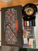 A ROULETTE BOARD WITH WHEEL, CHIPS, DICE ETC