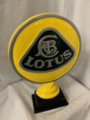 A LARGE CAST LOTUS SIGN ON A WOODEN BASE H:51CM