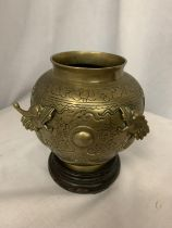 A CHINESE BRASS POT MANJI SYMBOL WITH DRAGONS ON A WOODEN STAND