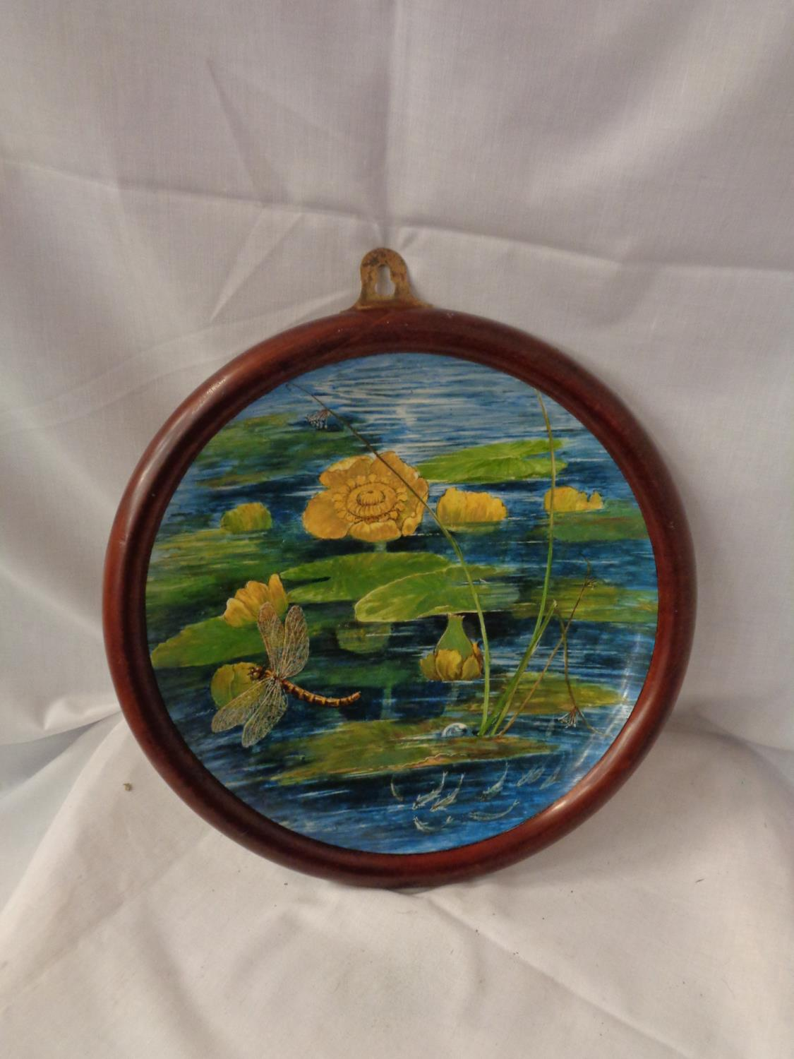 A FRAMED CHARGER DEPICTING A POND SCENEN WITH DRAGONFLY