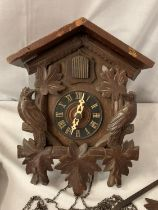 A CARVED WOODEN CUCKOO CLOCK WITH ONE WEIGHT