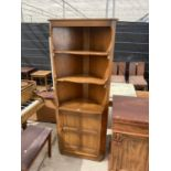 """AN ERCOL OPEN CORNER CUPBOARD WITH CUPBOARDS TO THE BASE, 27"""" WIDE"""