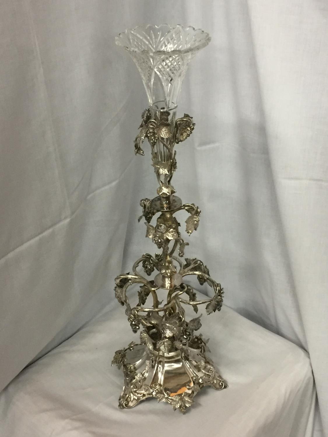 AN ORNATE SILVER PLATED EPERGENE WITH GLASS FLUTE HEIGHT 65CM