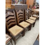 A SET OF FOUR OAK LADDERBACK DINING CHAIRS WITH RUSH SEATS
