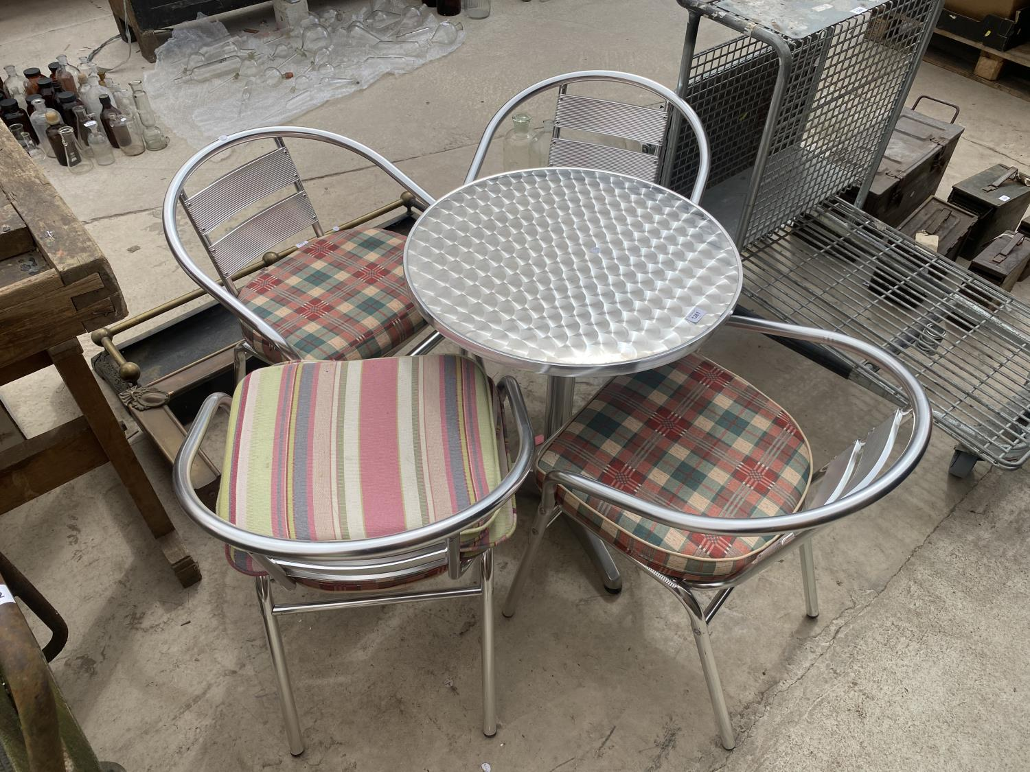 A STAINLESS STEEL BISTRO SET WITH ROUND TABLE AND FOUR CHAIRS