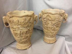 A PAIR OF HEAVILY CARVED ORIENTAL VASES WITH ELEPHANT DESIGN TWIN HANDLES 30CM HIGH