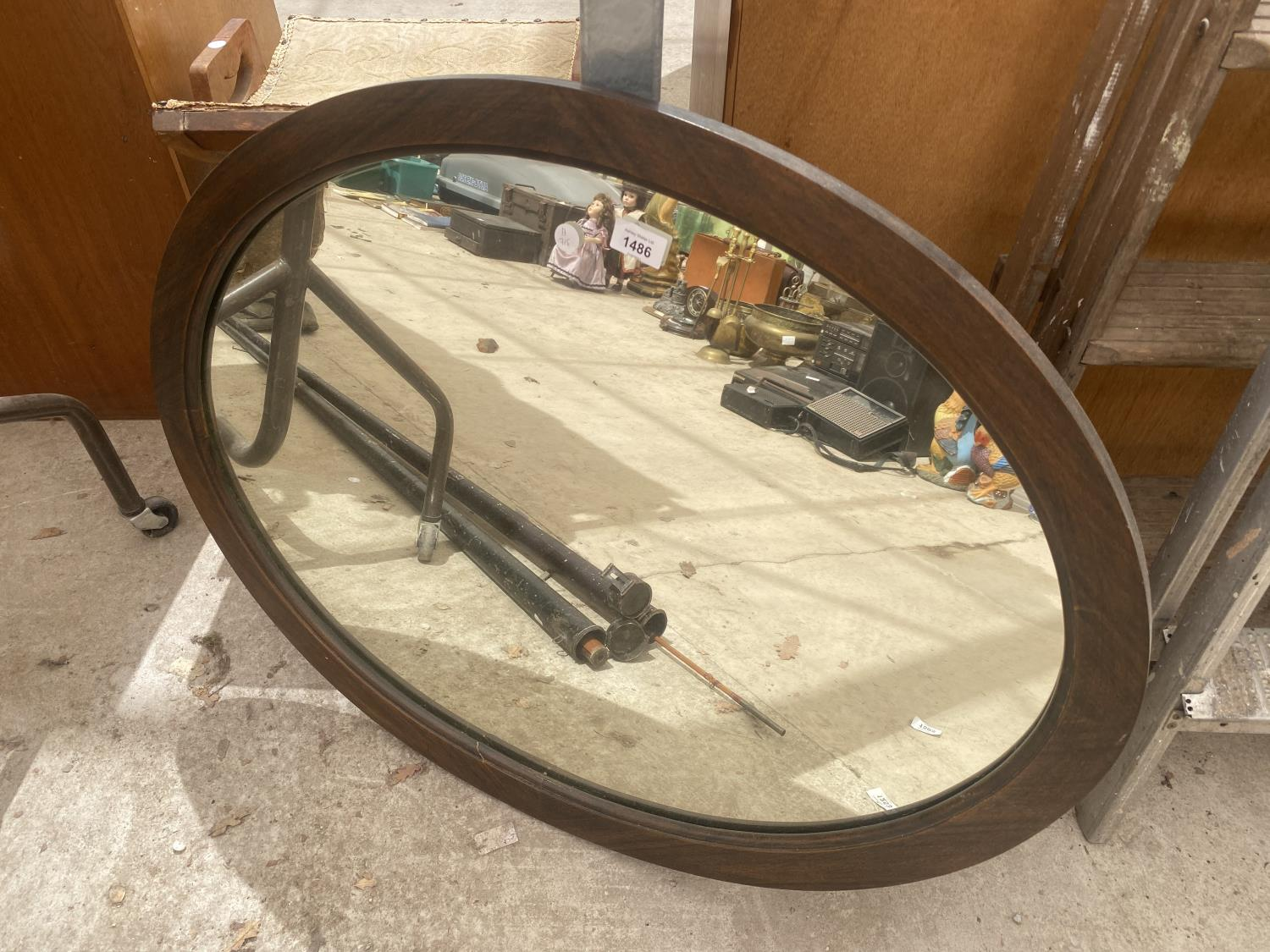 A WOODEN FRAMED OVAL MIRROR