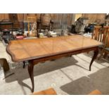A MAHOGANY EXTENDING DINING TABLE ON CARVED CABRIOLE SUPPORTS