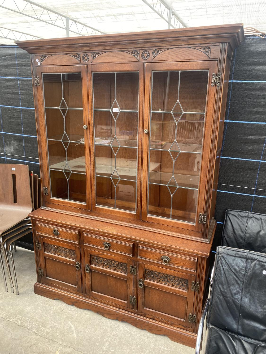 AN OAK OLD CHARM GLAZED AND LEADED CABINET ON BASE ENCLOSING THREE DRAWERS AND THREE CUPBOARDS, 52.