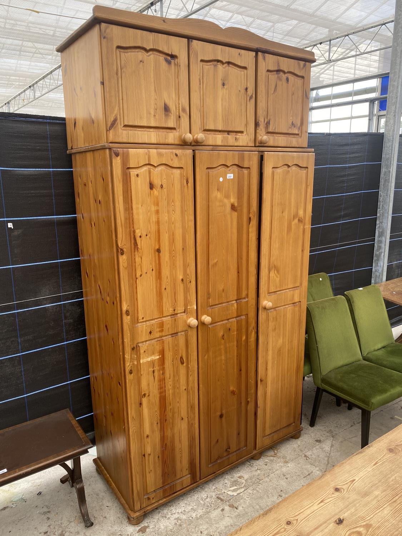 A MODERN PINE THREE DOOR WARDROBE