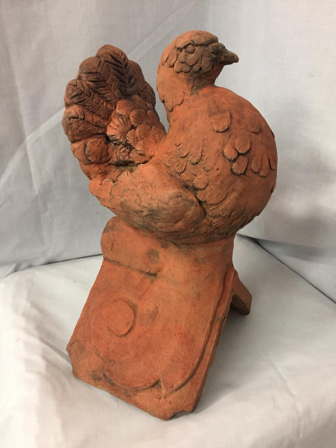 A TERRACOTTA ROOF TILE FINIAL OF A DOVE