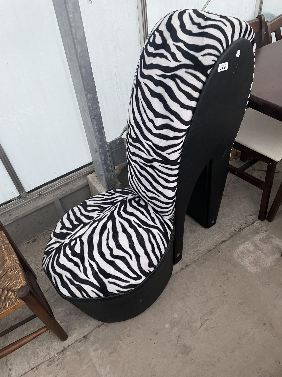 A FEATURE CHAIR IN THE FORM OF A HIGH HEEL SHOE WITH ZEBRA SKIN DESIGN FINISH