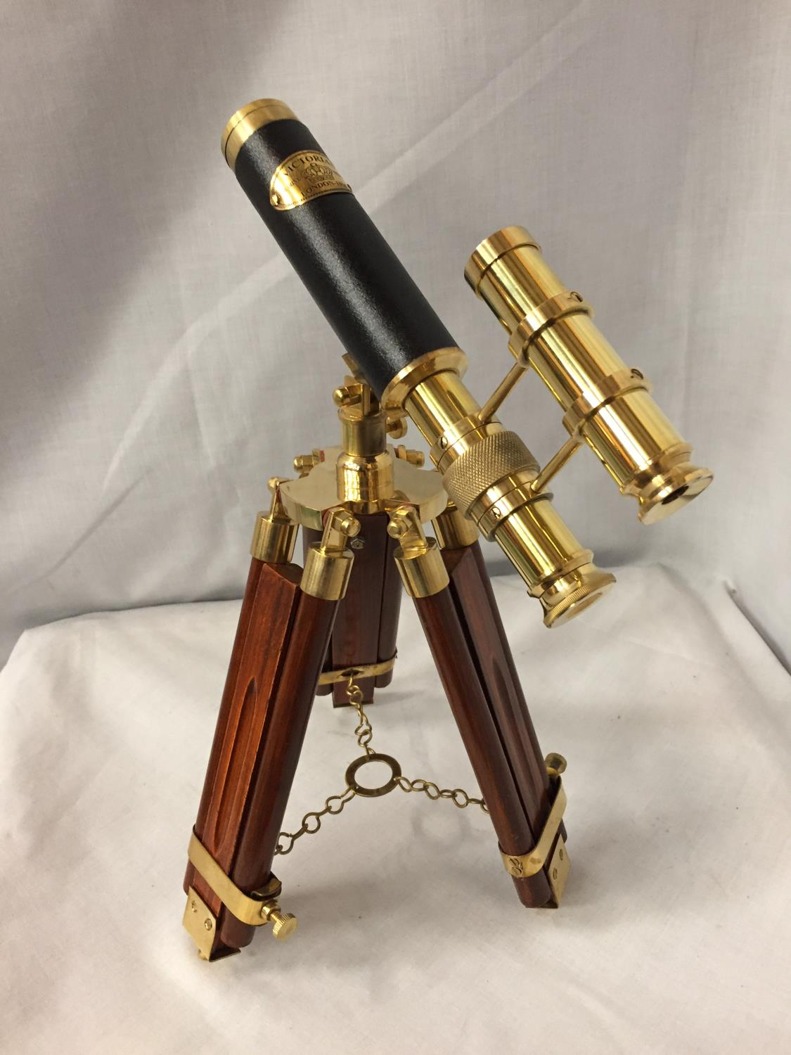 A BRASS AND LEATHER TELESCOPE ON A WOODEN TRIPOD STAND, 34CM HIGH