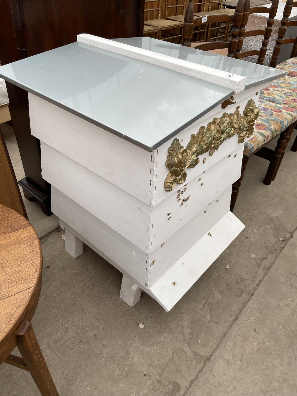 A FOUR TIER WHITE PAINTED FORMER BEEHIVE, DECORATED WITH BEES AND FLOWERS