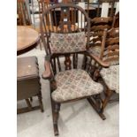 A REPRODUCTION WINDSOR ROCKING CHAIR WITH TURNED UPRIGHTS, BEARING LABEL 'R.E.FORSTER, WARRINGTON'