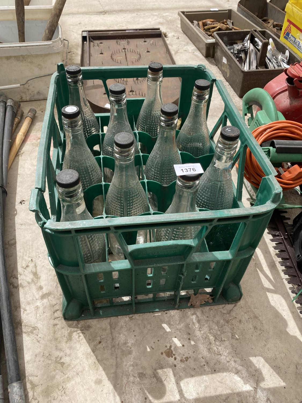 A BOTTLE CRATE CONTAINING TEN GLASS LUCOZADE BOTTLES