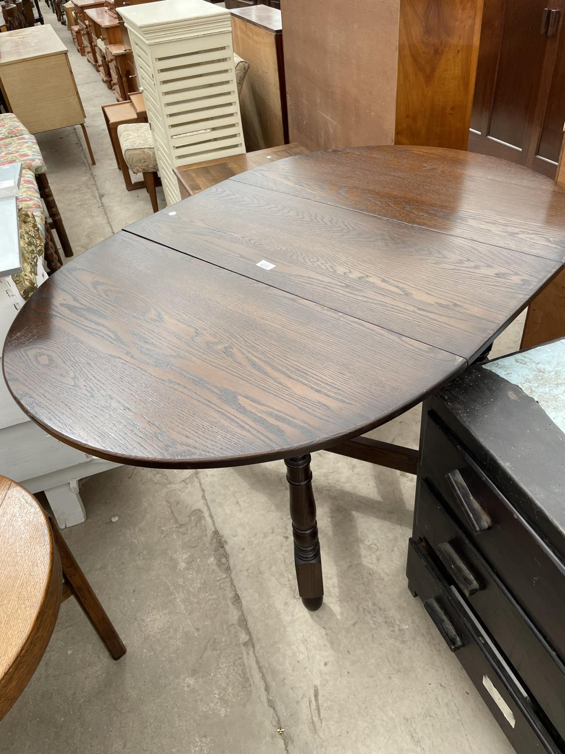A REPRODUCTION OAK GATELEG DINING TABLE ON TURNED LEGS, BEARING LABEL EDGAR MALTBY AND SON, CHESTER,