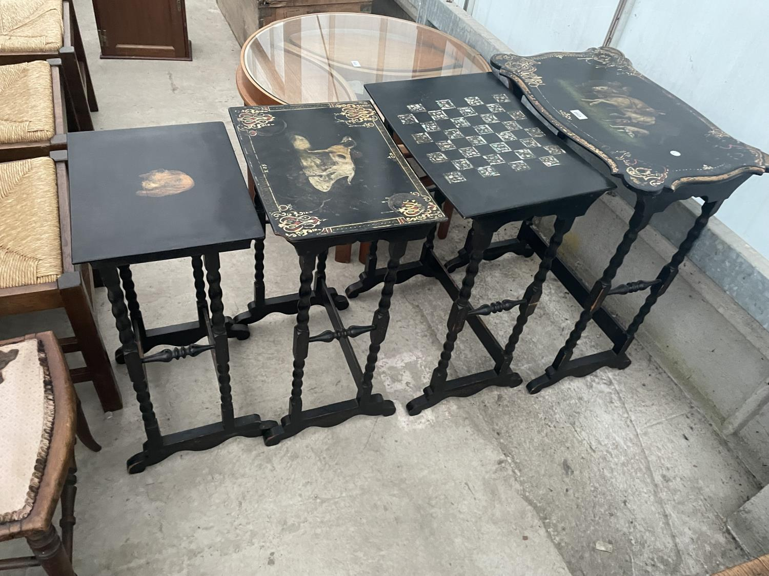 A NEST OF FOUR EBONISED AND PAPIER MACHE TABLES, THREE TABLES BEARING HUNTING IMAGE AND ONE WITH
