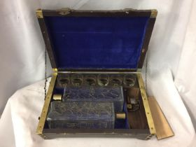 A WOODEN MUSICAL DRINKS BOX WITH BRASS BANDING CONTAINING TWO DECORATIVE GLASS BOTTLES WITH BRASS