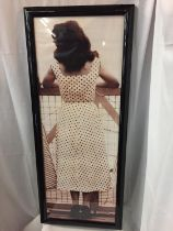 A LARGE BLACK FRAMED ORIGINAL KODAK PRINT OF A 1940'S LADY IN A POLKA DOT DRESS AND SEAMED STOCKINGS