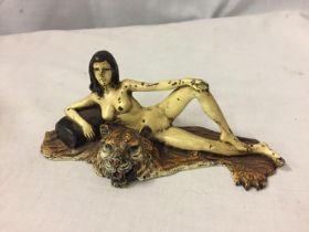 A COLD PAINTED BRONZE FIGURINE OF A NUDE LADY LYING ON A TIGER RUG
