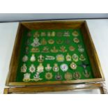 A GLAZED DISPLAY CASE CONTAINING FORTY FIVE BRITISH MILITARY BADGES, 34CM X 39CM