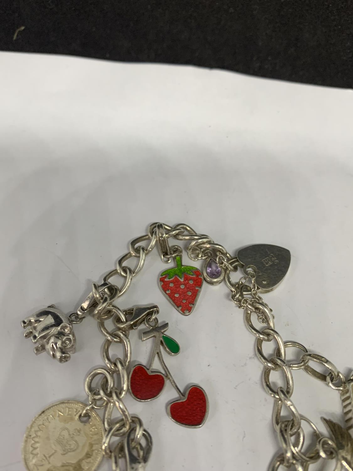 A HEAVY SILVER CHARM BRACELET WITH THIRTEEN CHARMS TO INCLUDE A STRAWBERRY, CHERRIES, DOVE ETC - Image 3 of 4