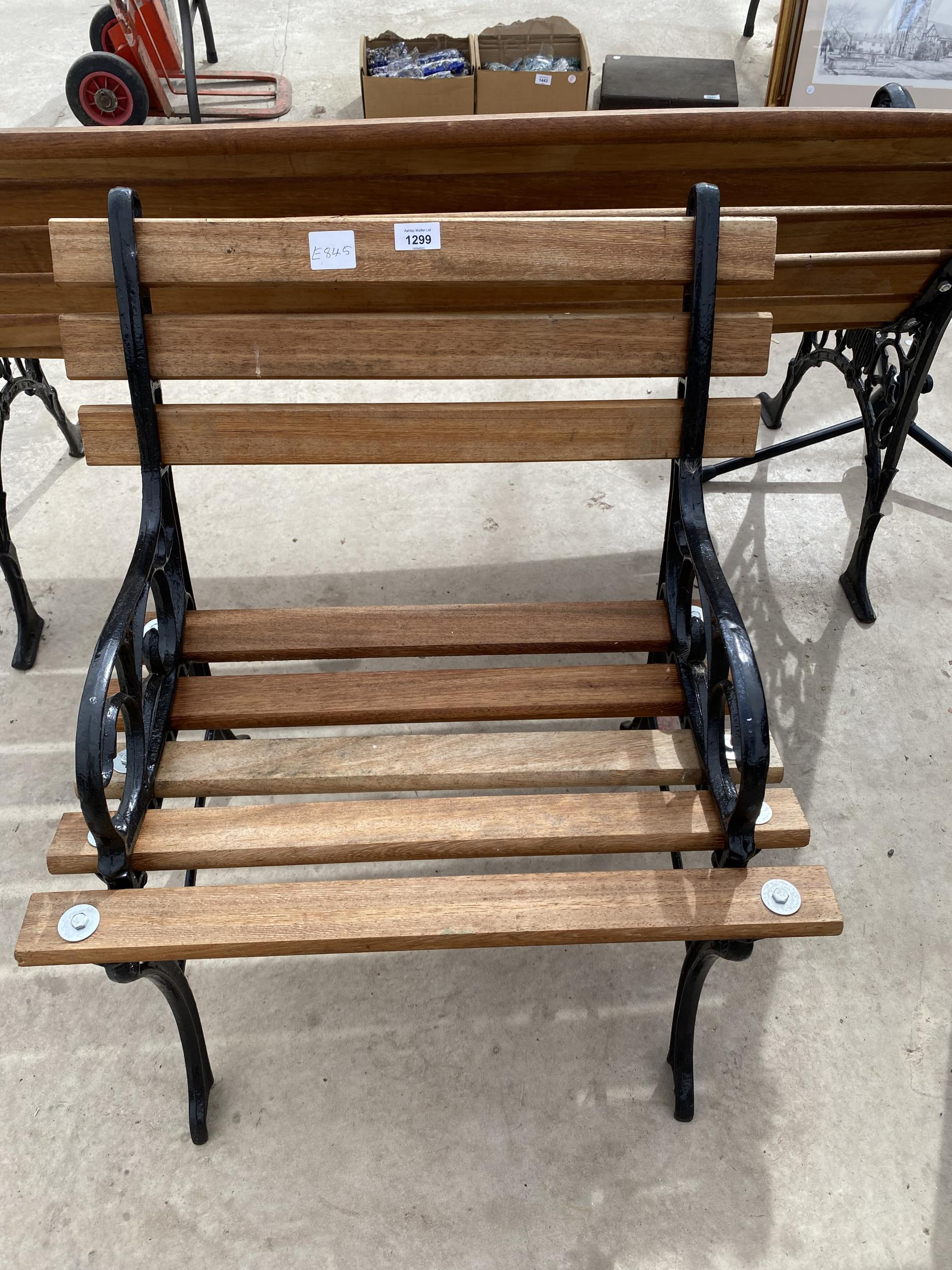 A WOODEN SLATTED GARDEN CHAIR WITH CAST IRON ENDS