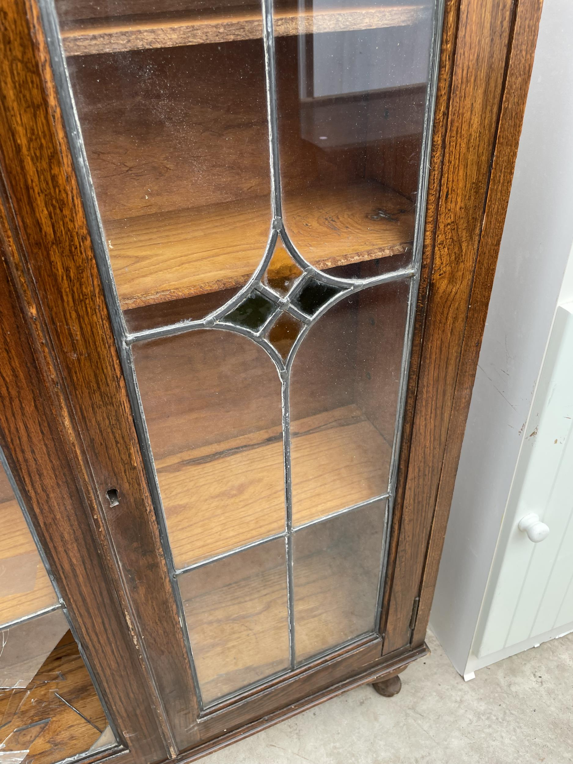 """AN EARLY 20TH CENTURY OAK GLAZED AND LEADED TWO DOOR BOOKCASE, 28.5"""" WIDE ON CABRIOLE LEGS - Image 4 of 6"""