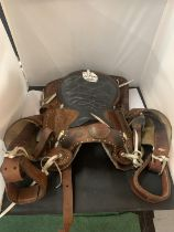 A TAN AND BLACK LEATHER U.S.A. WESTERN SADDLE WITH DECORATIVE DESIGNS AND STITCHING TOGETHER WITH