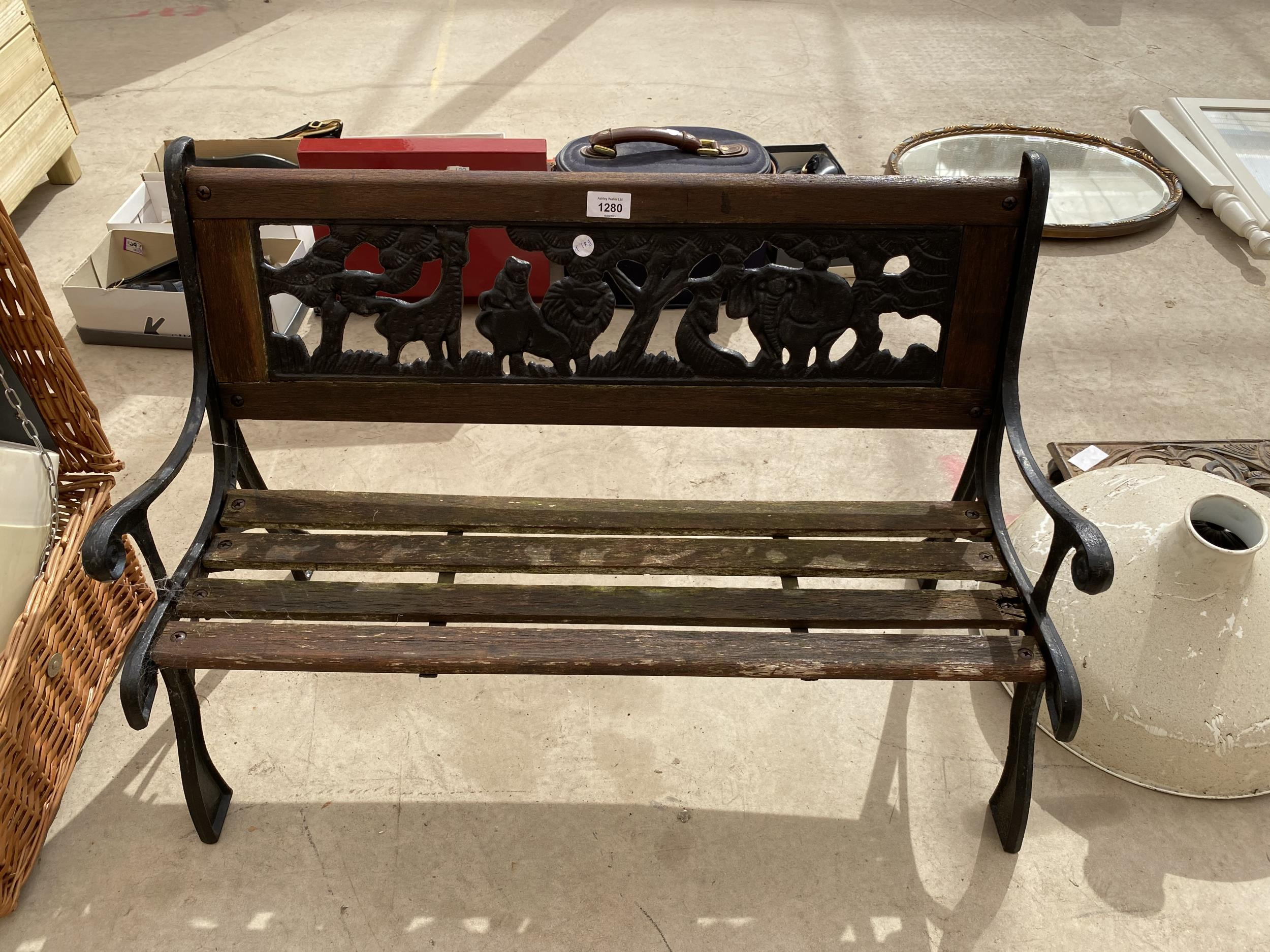 A SMALL CHILDRENS GARDEN BENCH WITH CAST BENCH ENDS AND A CAST BACK DEPICTING A SAFARI SCENE