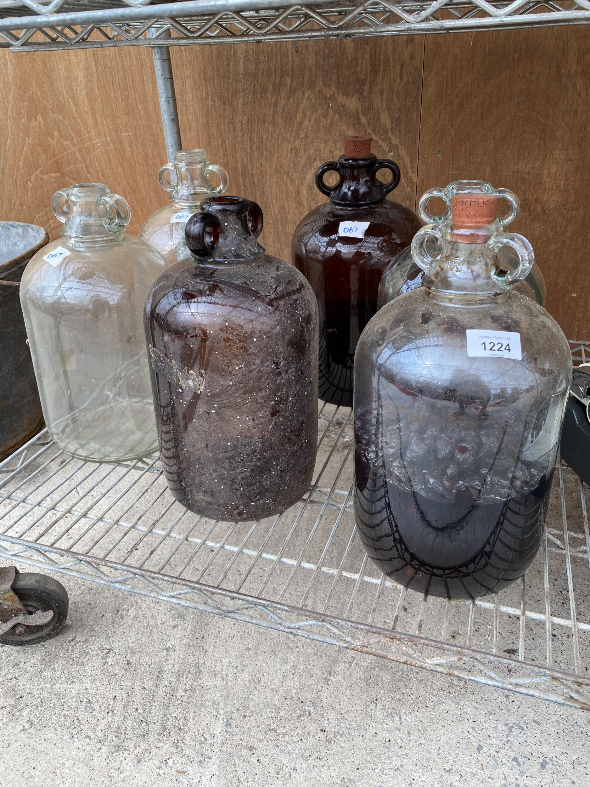 A GROUP OF SIX VINTAGE GLASS DEMI JOHNS