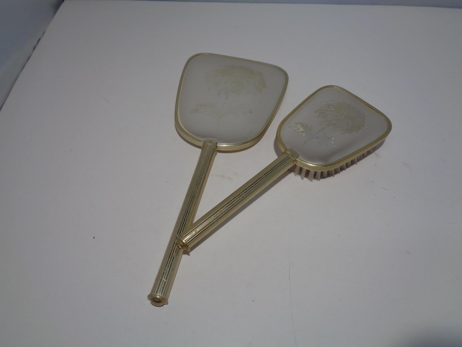 A DRESSING TABLE SET TO INCLUDE A HAND MIRROR AND MATCHING BRUSH