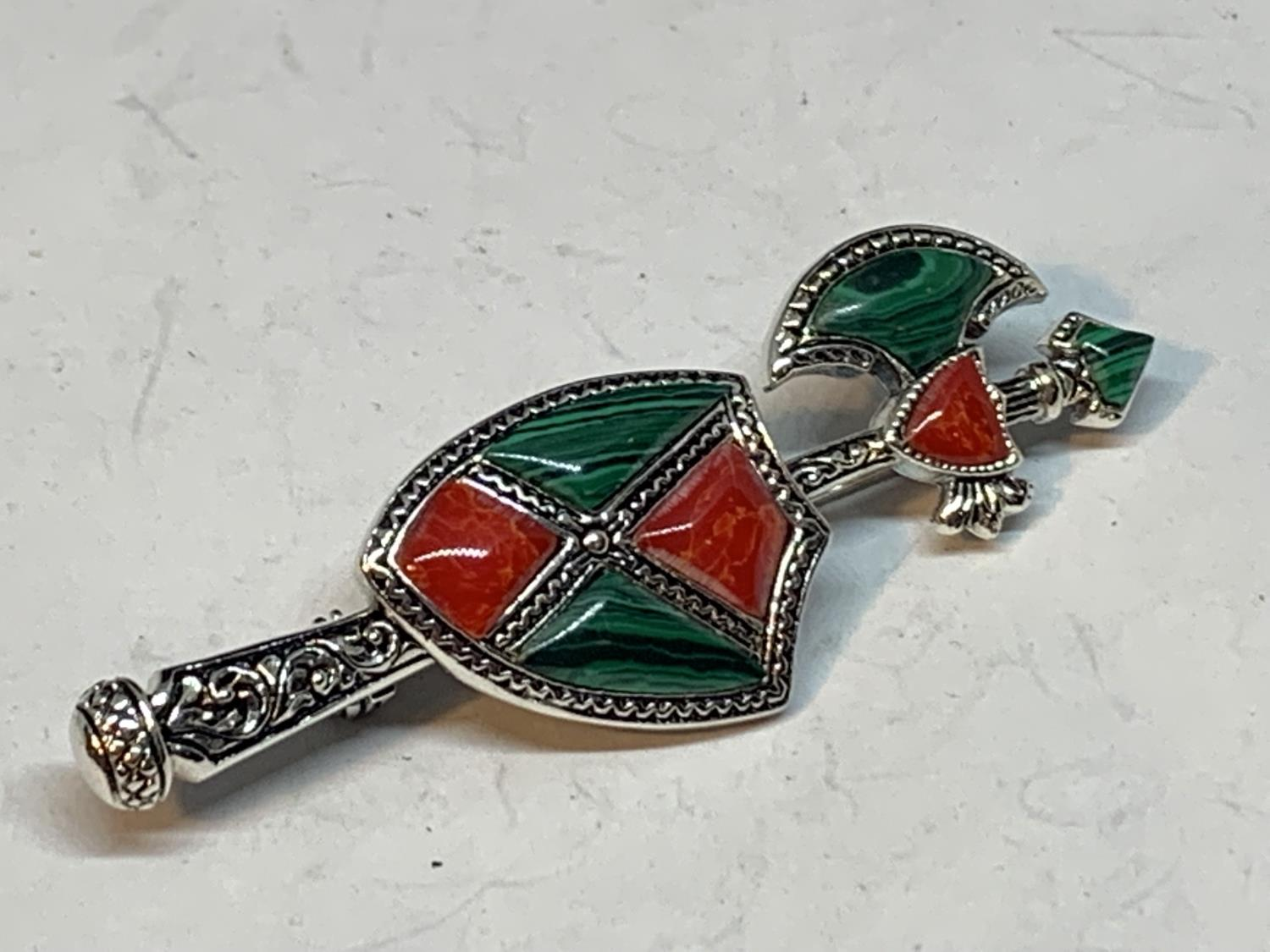 A SILVER BROOCH WITH GREEN AND RED ENAMEL AXE AND SHIELD DESIGN