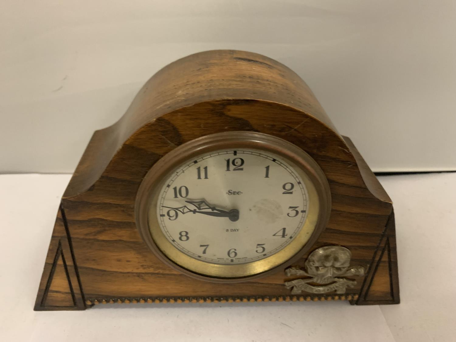 AN EIGHT DAY MANTLE CLOCK DECORATED WITH A DEATH OR GLORY MILTARY BADGE