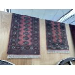 TWO RED PATTERNED FRINGED RUGS